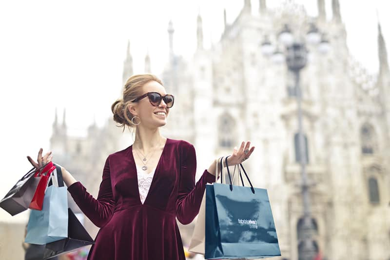 Woman wearing maroon velvet plunge neck long sleeved dress holding several branded paper bags.
