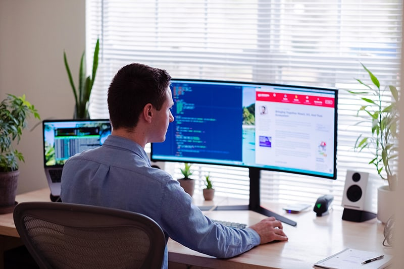 man working web development services on computer looking at monitor