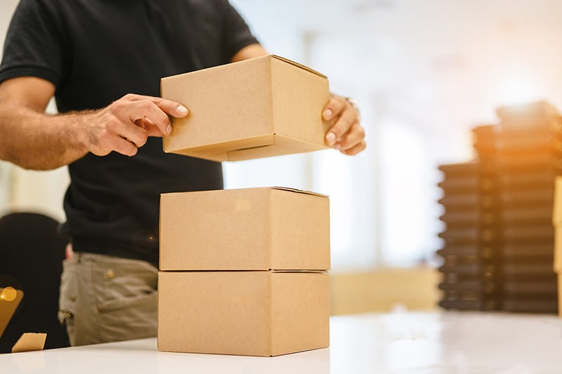 Person stacking boxed goods on a table