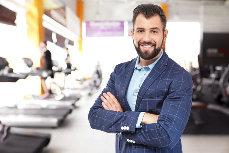 Franchise owner in suit with arms crossed standing in a gym