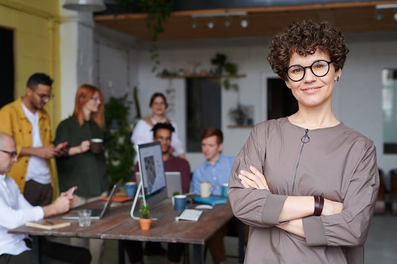 Woman standing in office wearing eyeglasses – with business colleagues behind her