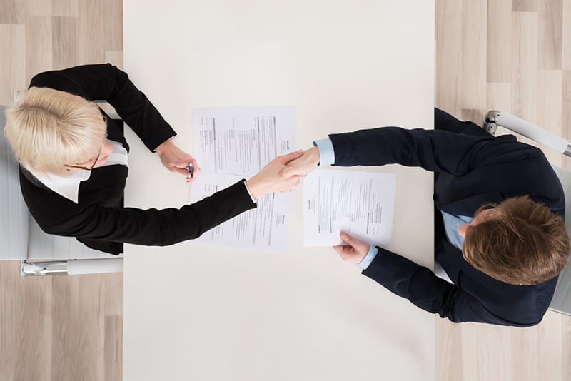 Two people shaking hands across a table and documents at a job interview