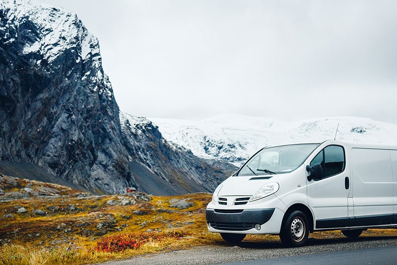 White commercial vehicle – business vehicle parked at side of road near mountains in Norway.