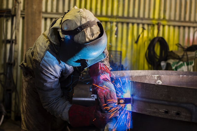 Man with safety gear doing welding and fabrication of the metal.