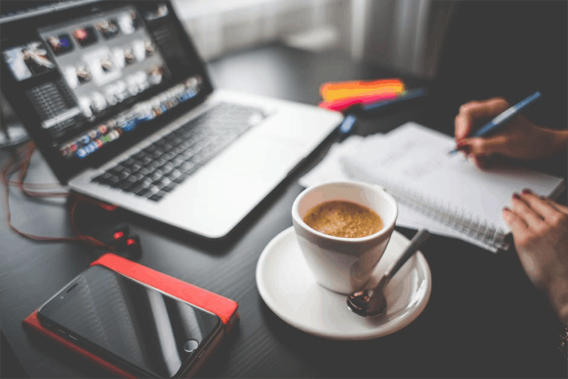 A laptop, mobile phone, coffee, and hand writing in the table