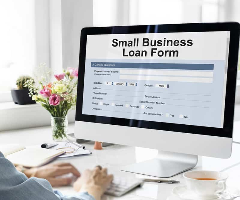 Person completing an application form for a Small Business Loan online