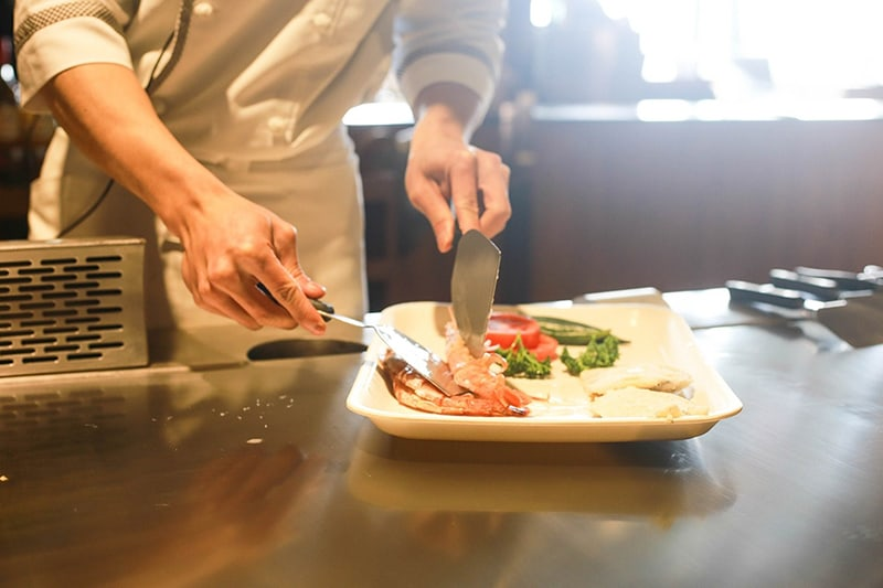 Restaurant chef plating up food for service