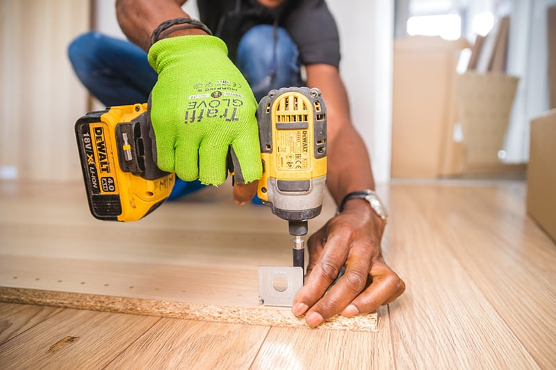 person doing home improvement with dewalt cordless impact driver on brown board