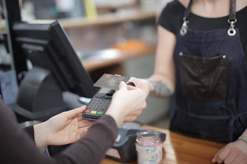 person holding credit card above credit card processing machine