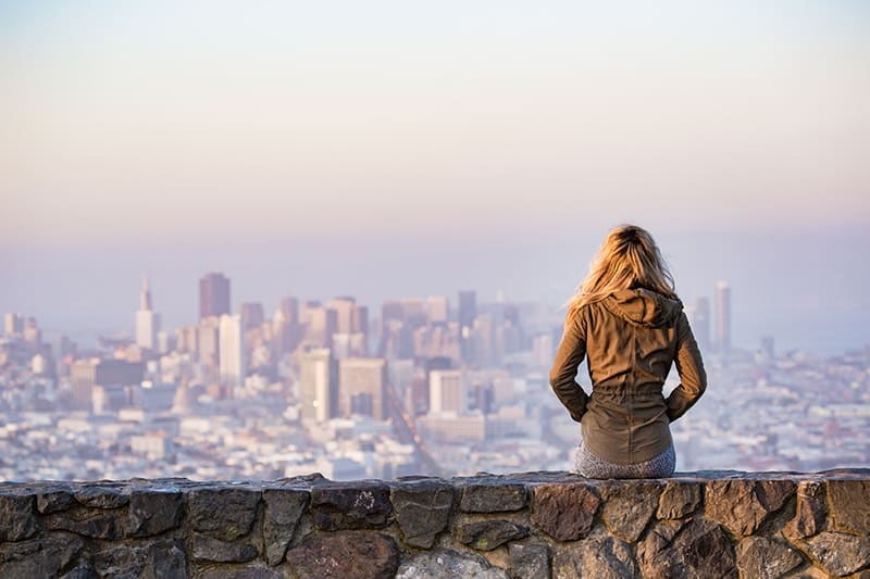 Woman on a rock wall looking out to urban environment - city