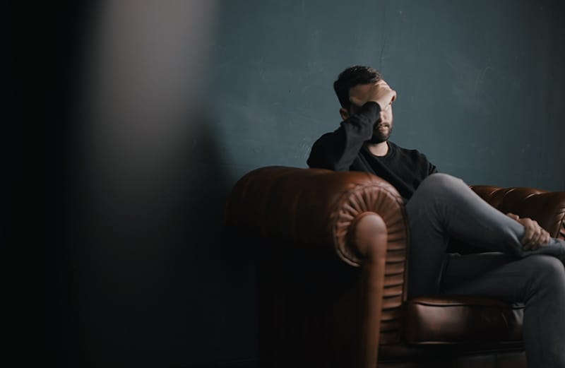 Man sitting on sofa holding head on hands – suffering with his mental health