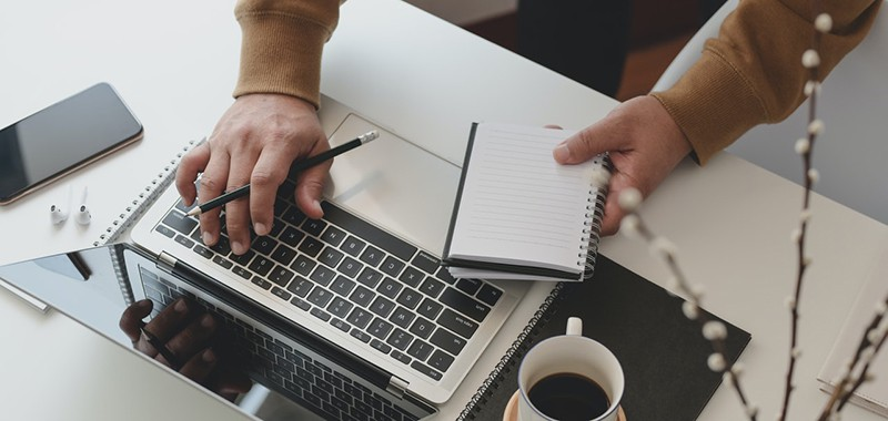 Person holding black pencil and notebook typing on laptop