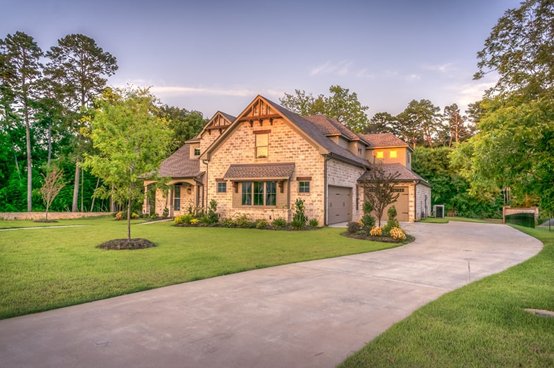 driveway leading to brick house set in landscaped garden