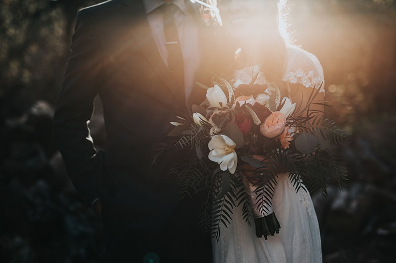 Wedding photo of groom standing next to bride holding bouquet of flowers