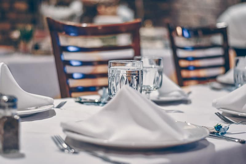 Depth of field photo of clear drinking glass on white table near plate in restaurant