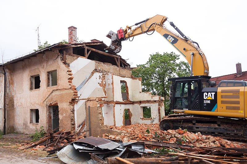 house demolition in progress by person in CAT 329E vehicle