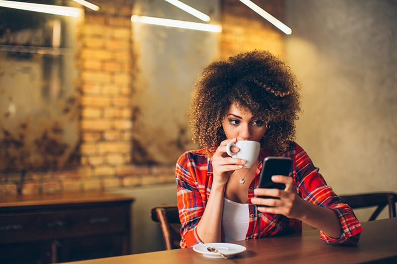 young woman looking at smartphone and having a drink