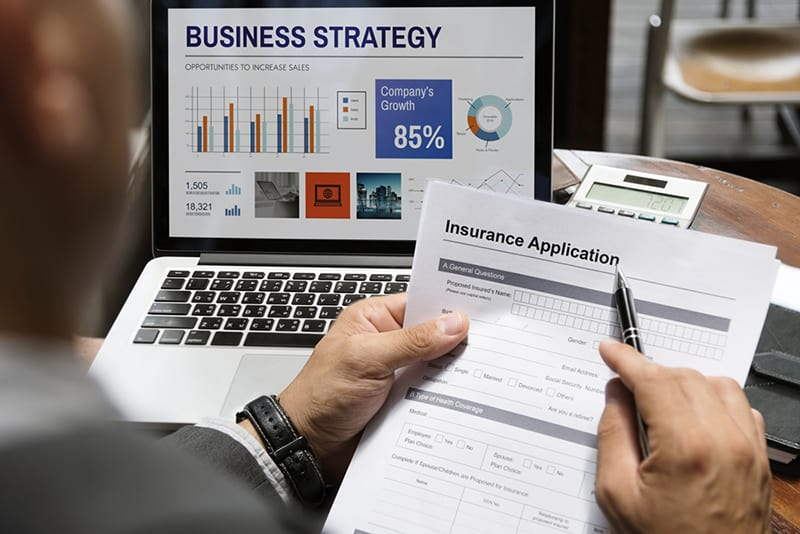 business man filling out insurance form with business strategy on laptop