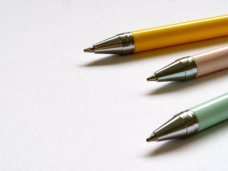 Three pens in yellow, pink and green colors.