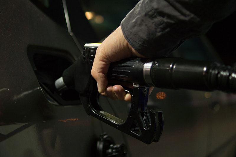 A man in a black sleeve putting fuel in vehicle