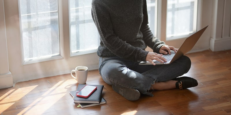 woman in grey sweater sitting cross legged on floor with laptop on knees
