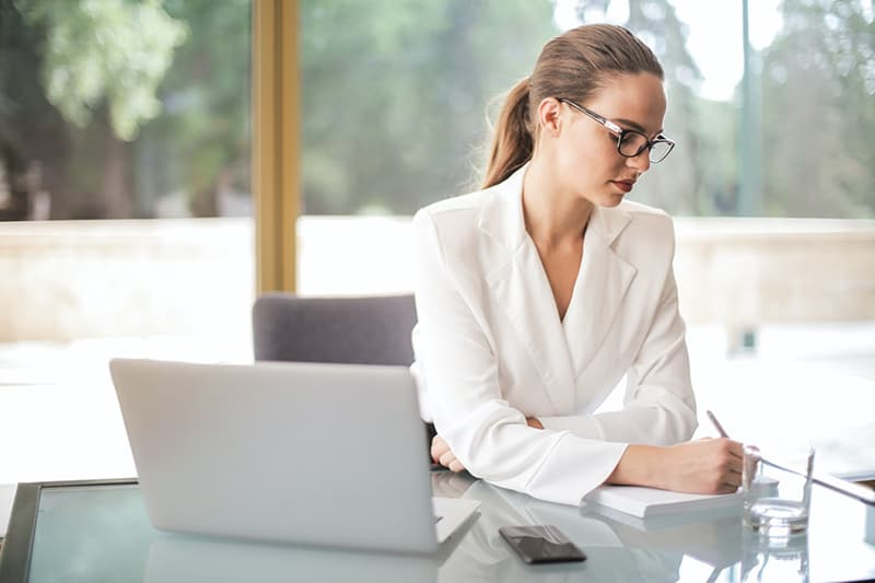 Woman working from home sat at desk writing on a notepad.