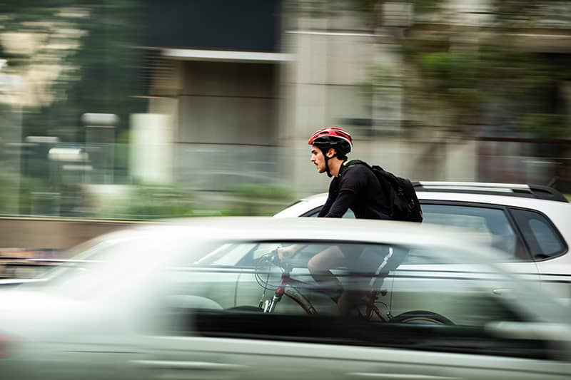 Man wearing a bike helmet and backpack on bicycle on road between cars