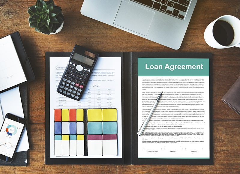 Loan agreement form with pen and calculator on the top of wooden table