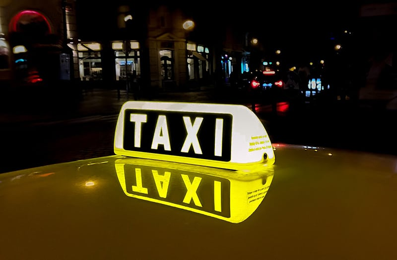 lit taxi signage reflected on the roof of a taxi cab