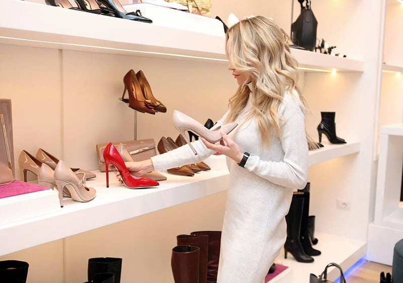woman in traditoinal business shoe store looking at and holding shoes