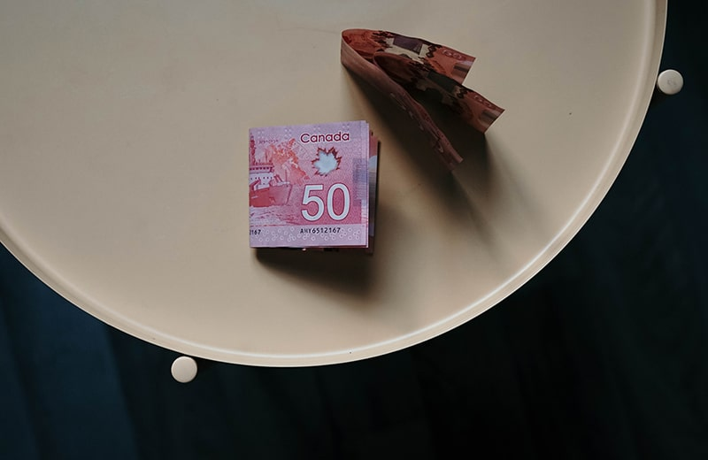 Several 50 Canadian dollar banknotes on a round table