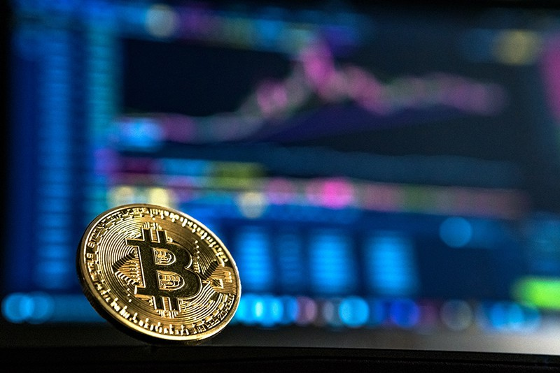 Bitcoin – cryptocurrency set against blurred image of forex trading charts
