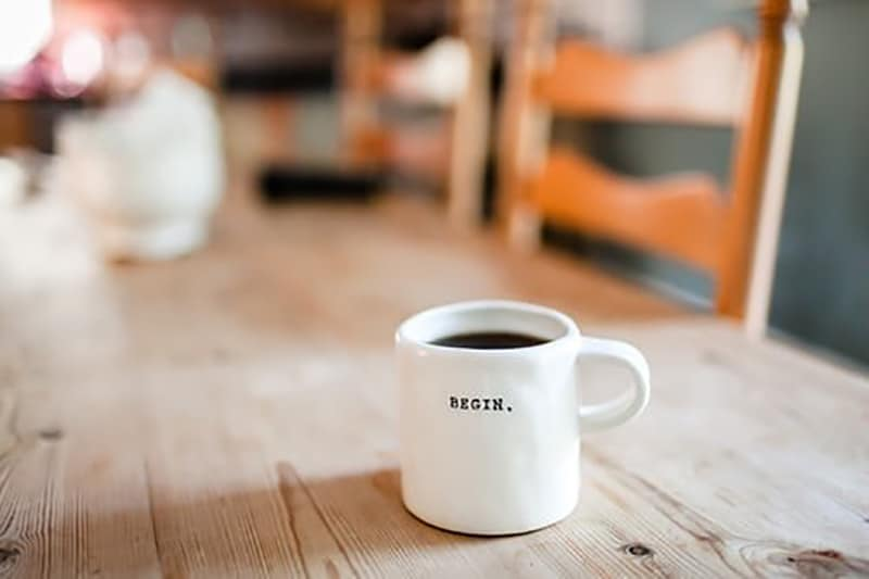 mug on table with the word begin on it