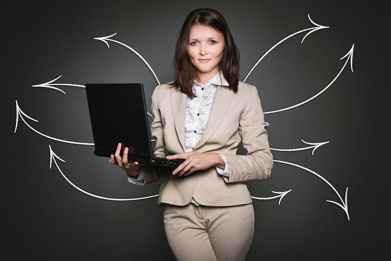 Woman in suit holding laptop