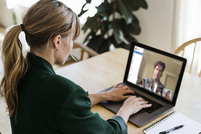 Woman wearing green blazer chatting to a person on video conference