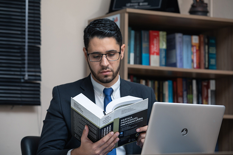 A lawyer with eyeglasses reading a book