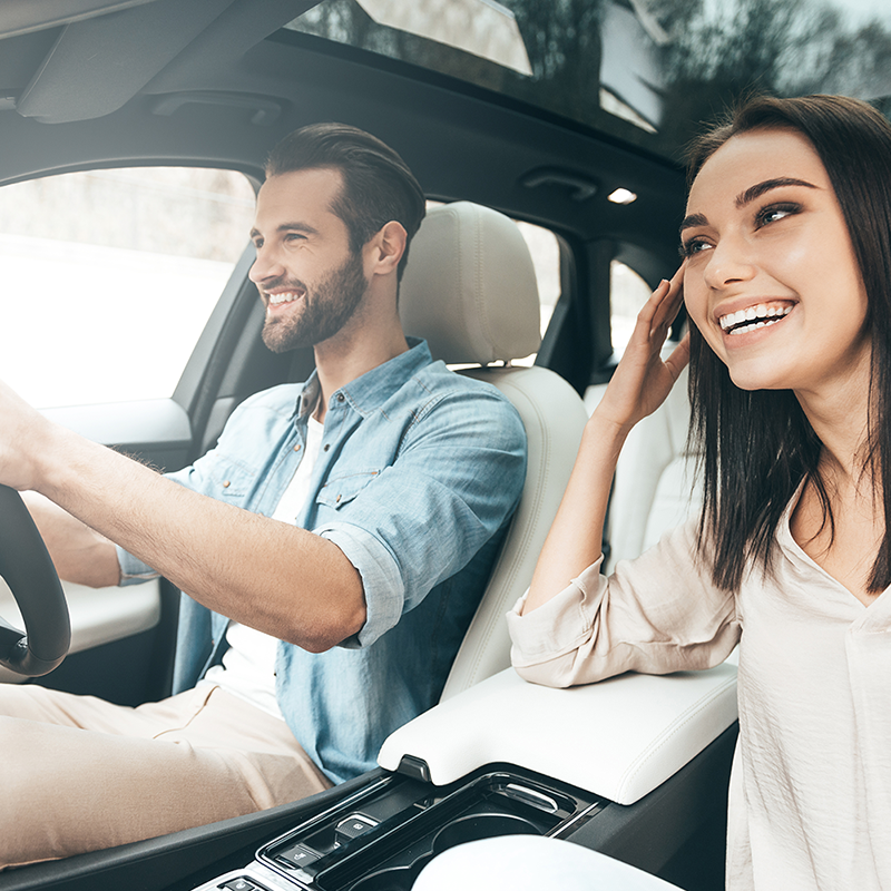 Man and woman driving in a rental car