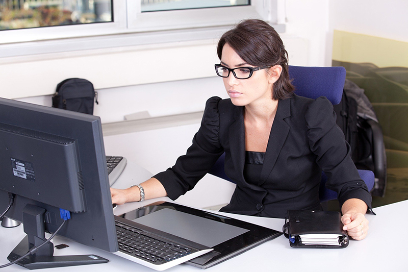 A business woman wearing eye glasses and black suits in front of computer