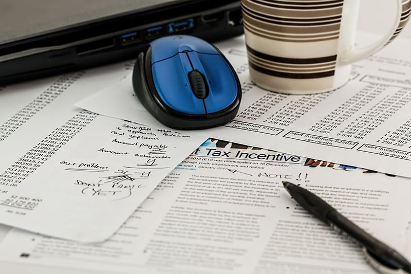 A blue wireless mouse, stripe cup, black pen, and tax incentives computation