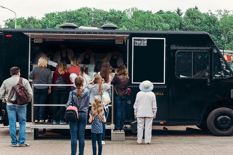 People standing in a queue at a food truck