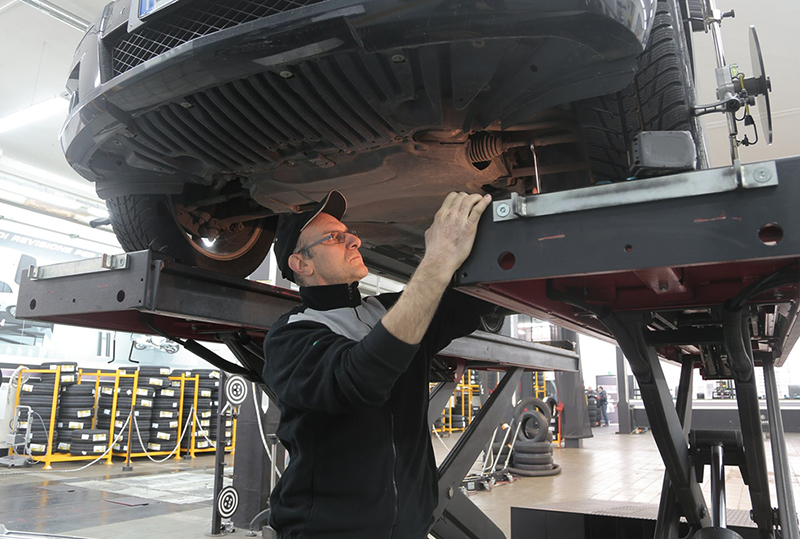 Man in black jacket working underneath a vehicle in car repair shop