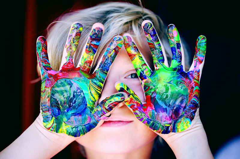 blur image of boy with paint on hands in a child care setting
