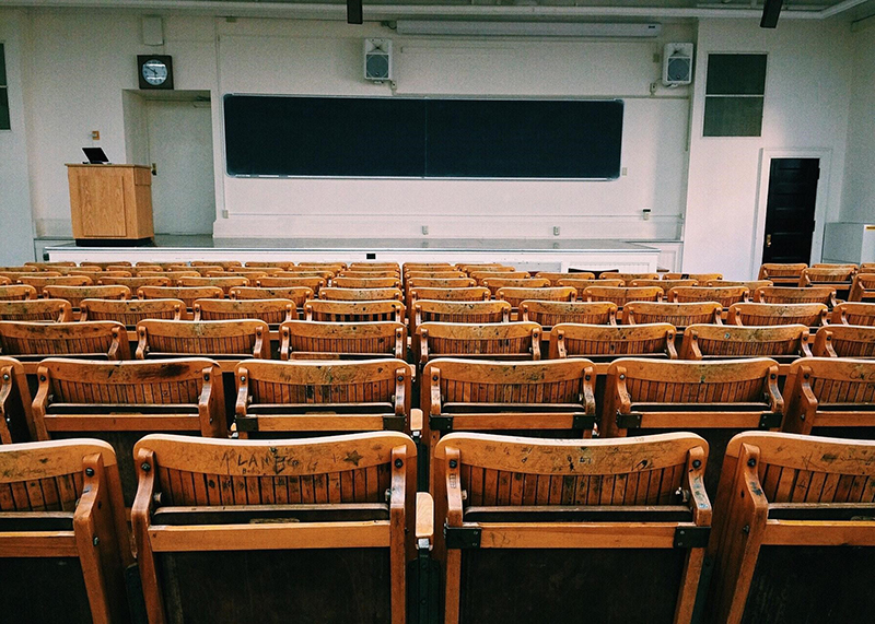 An empty classroom with black board and wooden arm chairs