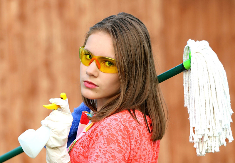Woman holding mop and cleaning products to clean workplace