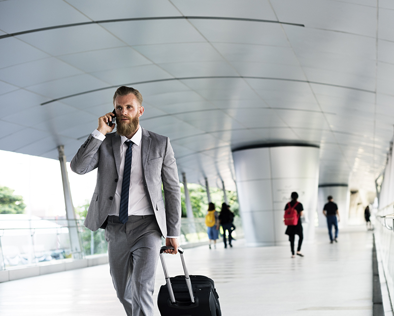 A business man pulling his luggage while calling on his mobile phone