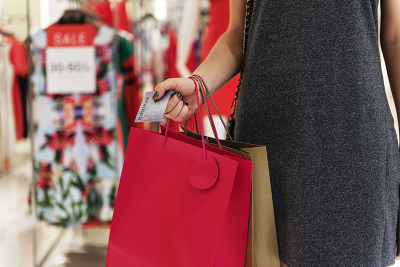 A woman in grey dress carrying paper bags from shopping while holding credit card