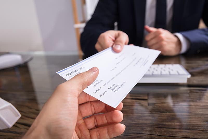 A businessman giving check to another person