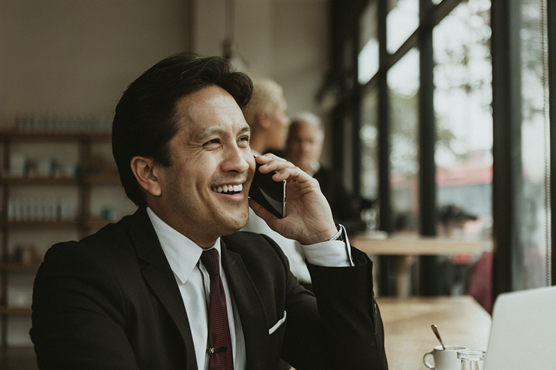 happy businessman speaking on phone in café