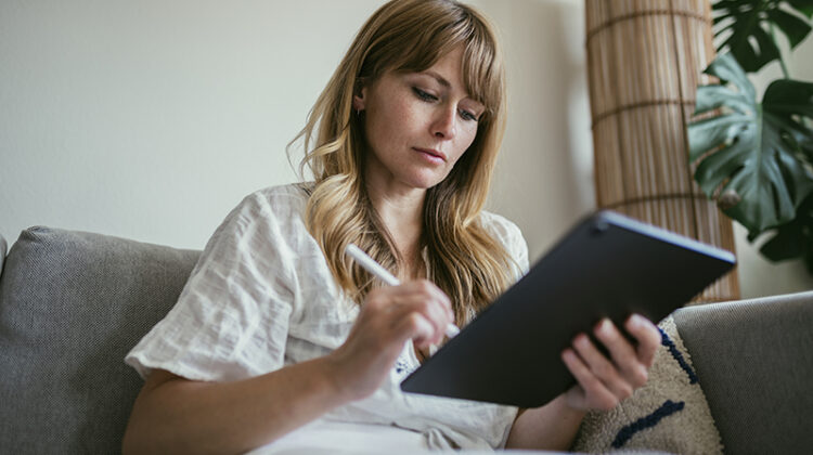 Woman using a stylus writing on a digital tablet while sitting in the couch