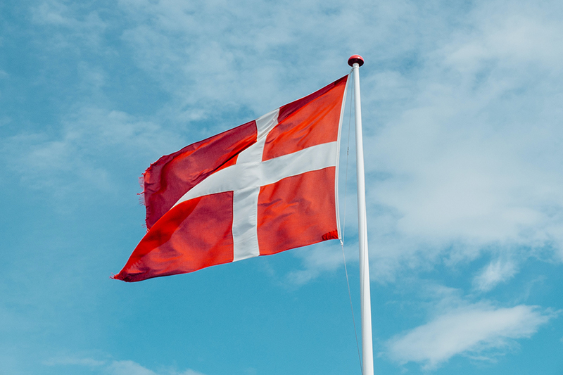 Danish Flag - red and white flag on flag pole - blue sky and clouds in background
